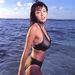 Alluring asian beauty with large heavy breasts in a bikini